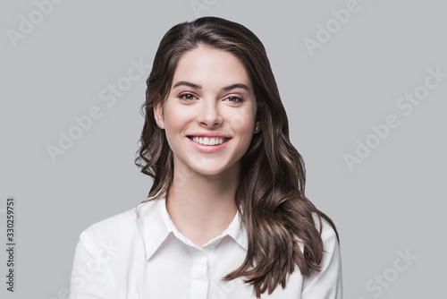 Obraz Beautiful young business woman portrait, Smiling cute girl with long hair studio shot, Isolated on gray background	 - fototapety do salonu