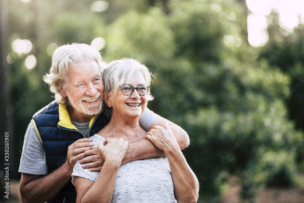 Fototapeta Old mature retired senior people smile and enjoy the love couple during outdoor leisure activity together - green forest and wood in background for environment concept