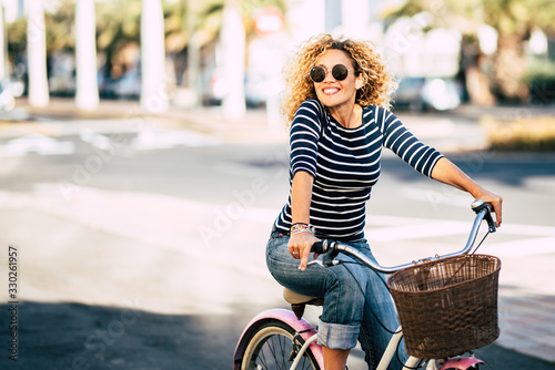 Fototapeta Beautiful and cheerful adult young woman enjoy bike ride in sunny urban outdoor leisure activity in the city - happy people portrait - trendy female outside having fun obraz