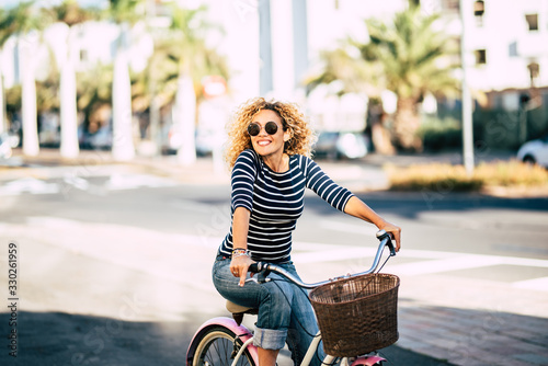 Beautiful and cheerful adult young woman enjoy bike ride in sunny urban outdoor Canvas