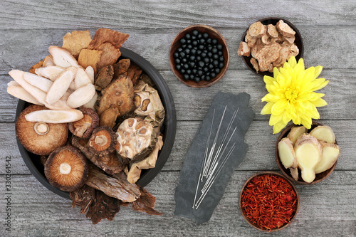 Photo Traditional Chinese herbs, acupuncture needles and tablets to boost chi level used in herbal medicine on rustic wood background