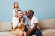 canvas print picture - Portrait of happy multiethnic family sitting on couch at home and looking at camera. Black father, white mother and two daughters. Eldest leaning on mother from behind. Youngest is in father's arms.