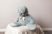 A Plush Hare Is Sitting On A Blanket. Cute Children's Toy. Grey Toy Hare.