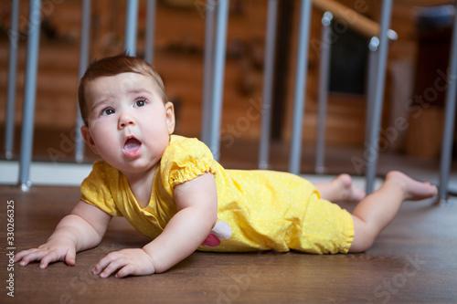 Photo Side view of baby lying on hardwood floor in children room, yellow bodysuit