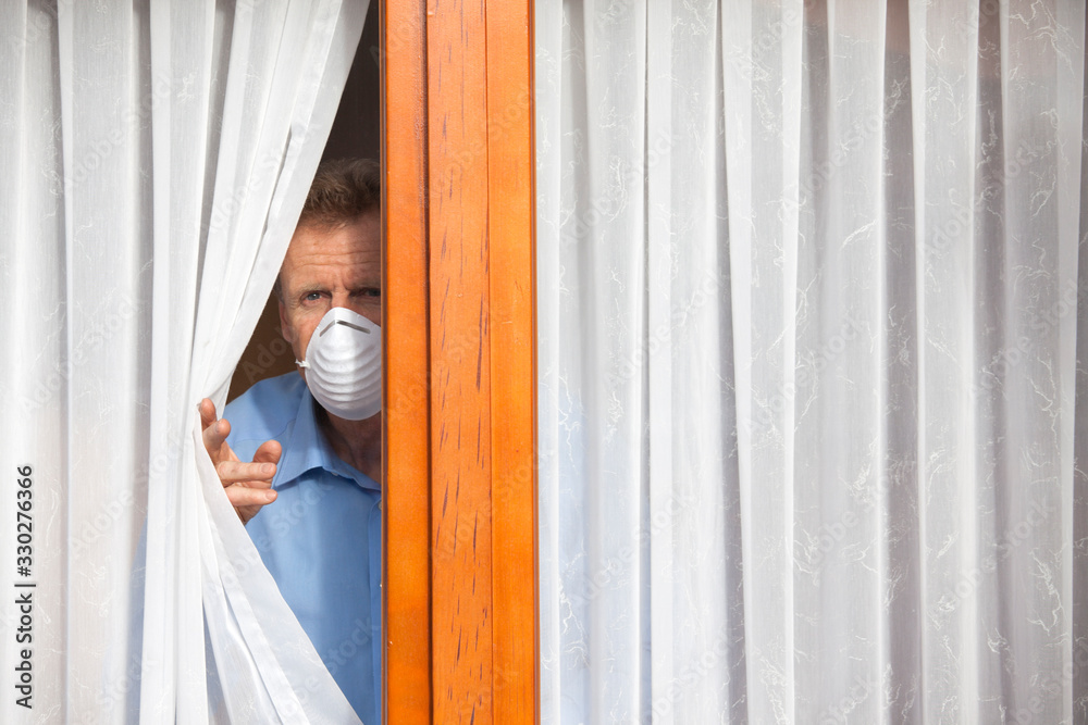 Fototapeta Mature man put under quarantine at home or at a hospital because of an infection or coronavirus looking sorrowful out of  a window