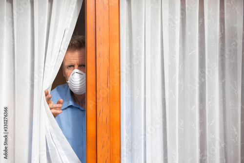 Obraz Mature man put under quarantine at home or at a hospital because of an infection or coronavirus looking sorrowful out of  a window - fototapety do salonu