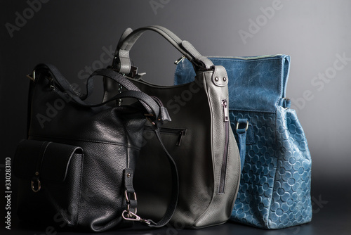 Photo leather handbags of different colors on a black background side view, women's vi