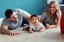 Pretty Young Parents Playing With Baby Son While Sitting On The Floor At Home.