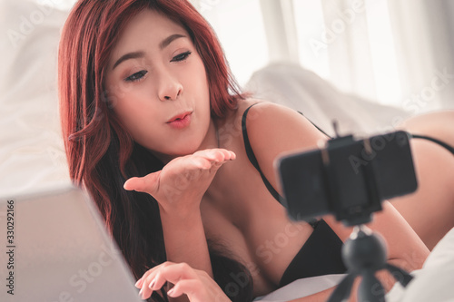 Woman with underwear using phone to boardcast seductive webcam live show online