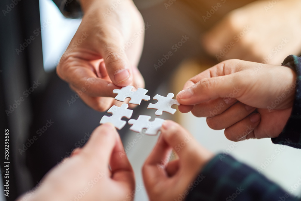Fototapeta Closeup image of a group of people holding and putting a piece of white jigsaw puzzle together