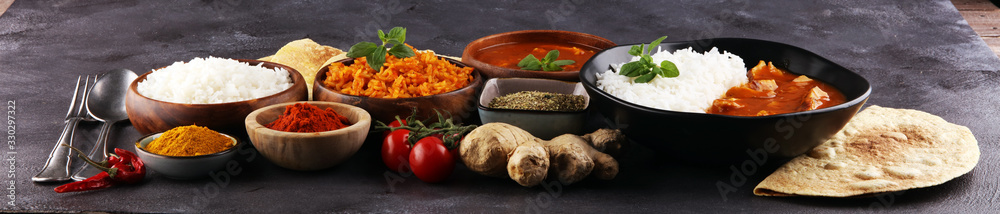 Fototapeta Chicken tikka masala spicy curry meat food in pot with rice and naan bread. indian food on table