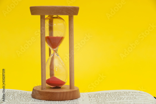 Photo Red sand hourglass on top of open Holy Bible in the Book of the Prophet Ezekiel chapter 7 verse 7