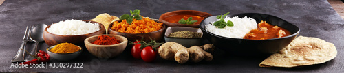 Fototapeta Chicken tikka masala spicy curry meat food in pot with rice and naan bread. indian food on table obraz