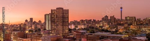 A beautiful and dramatic panoramic photograph of the Johannesburg city skyline, taken on a golden evening after sunset.