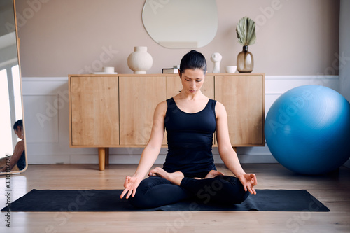 Young attractive smiling woman practicing yoga, sitting in Half Lotus exercise, Ardha Padmasana pose, working out, wearing sportswear, meditation session, indoor full length, home interior
