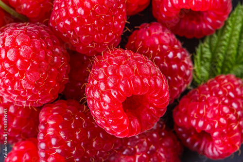 juicy fresh natural raspberries on a dark stone background