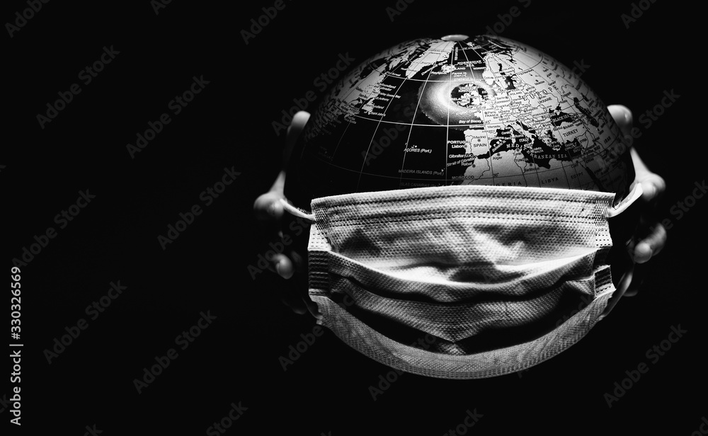 Fototapeta Hands of little child holding globe sphere, planet map covered with medical protective mask isolated on black background. Concept of COVID-19 pandemic infection. Black and white image