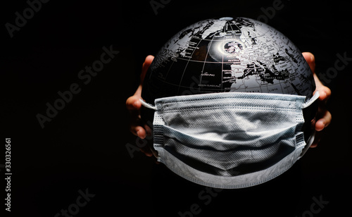 Obraz Hands of little child holding globe sphere, planet map covered with medical protective mask isolated on black background. Concept of COVID-19 pandemic infection - fototapety do salonu