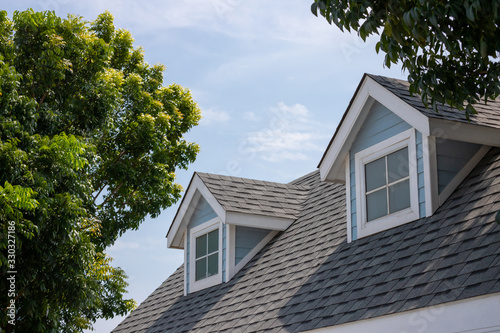 Obraz Roof shingles with garret house on top of the house among a lot of trees. dark asphalt tiles on the roof background - fototapety do salonu