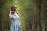 Fototapeta Las - Girl in blue dress in green park