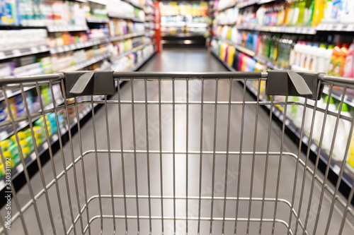 Shopping trolley cart moving in supermarket with motion blur aisle background Canvas Print