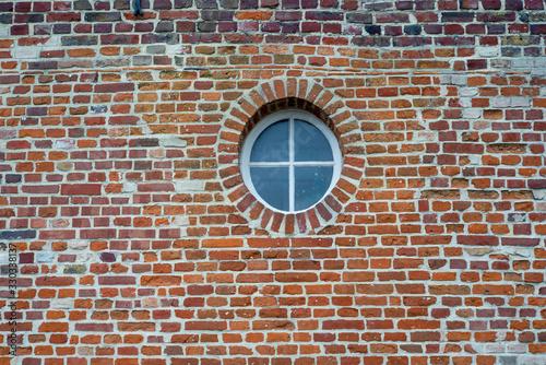Obraz na plátně fenêtre ronde avec croisillon dans un mur de briques.