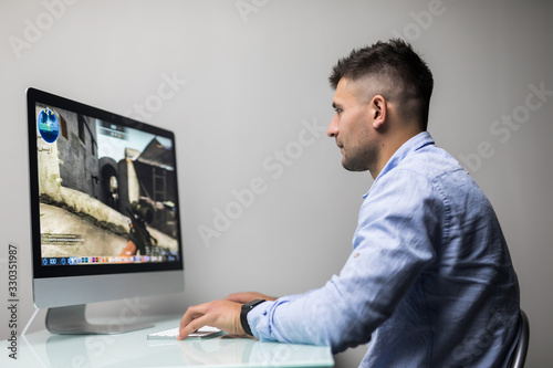 Photo Professional gamer playing in first-person shooter online video game on his personal computer