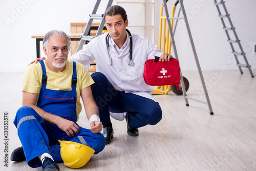 Young male doctor and old contractor in first aid concept Canvas Print