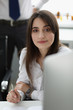 Portrait of gorgeous designer sitting in modern office and looking at camera with gladness and joy. Beautiful woman holding white writing pen. Blurred background