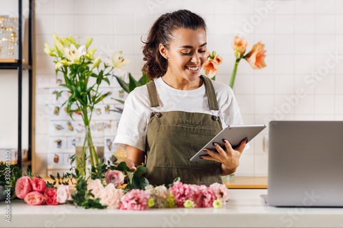 Leinwand Poster Smiling florist woman holding a digital tablet while standing at the counter in