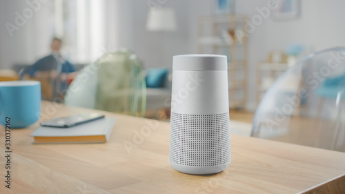 Obraz Close Up Shot of a Modern Silver Wireless Speaker Standing on a Table at Home. Man in the Background Sitting on the Sofa. - fototapety do salonu