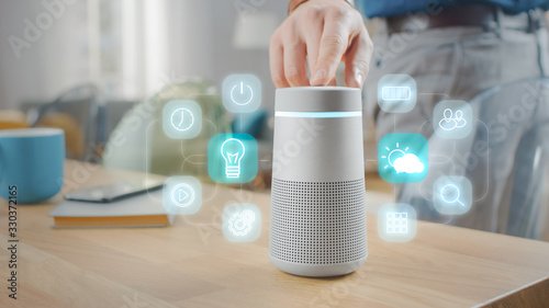 Photo Man Turns On Smart Speaker with Active Artificial Intelligence Assistant with Futuristic Screenless Interface with Different Icons and Symbols