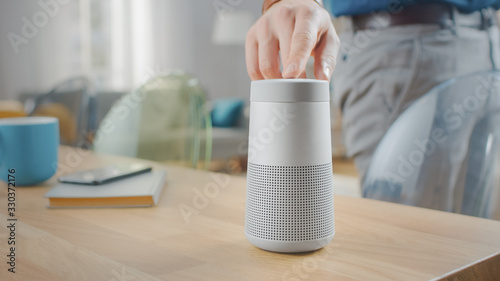 Photo Man Turns On Smart Speaker that Activates Artificial Intelligence Assistant