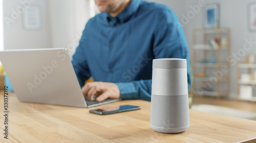 Obraz Close Up Shot of a Modern Silver Bluetooth Speaker Standing on a Table at Home. Man in the Background Sits at the Table and Works on His Laptop. Smartphone Lies on a Table Next to Him. - fototapety do salonu