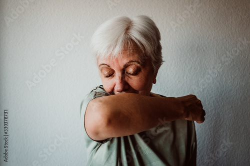 .White-haired, middle-aged woman with coronavirus symptoms coughing correctly on Wallpaper Mural