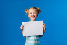 Baby Girl Holding A White Sheet.Cute Little Girl With A White Sheet Of Paper.blue Background.space For Text.A Little Girl Holds An Empty Piece Of Paper