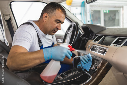 Foto Man cleaning upholstery and interriour of his vehicle