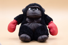 Stuffed Toy Gorilla Boxer With Angry Face Posing On A Pale Yellow Background