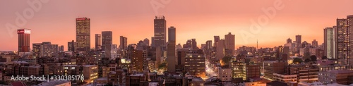 A beautiful and dramatic panoramic photograph of the Johannesburg city skyline  taken on a golden evening after sunset.