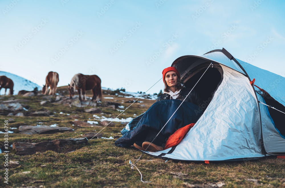 Fototapeta girl relax in campsite, tourist in camp tent on mountain nature, hiker woman enjoys wild horses on valley camping trip
