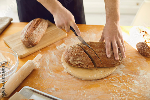 Hands cutting fresh homemade bread on a table in a bakery kitchen Fototapeta