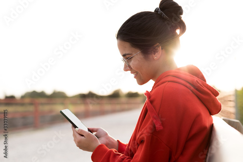 Obraz Young woman with glasses on her twenties chatting on her phone while sitting in a bench of a park. She is smiling and wearing a red sweater and a ponytail. She is backlit with daylight at sunset - fototapety do salonu