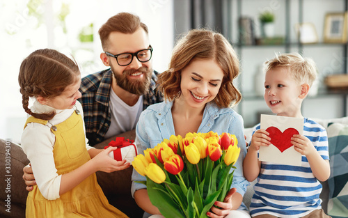 Fototapeta happy mother's day! father and children congratulate mother on holiday  . obraz