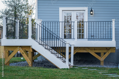 Fototapeta View of a classic backyard wooden deck with black metal balustrades railing and white columns on an American single family home obraz