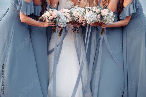 Cuadros en Lienzo Beautiful blue dridesmaids dresses and bride with fresh hydrangea bouquets