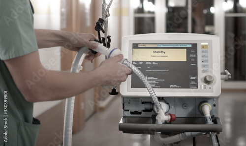 Obraz Nurse setting the pulmonary ventilator, medical machine used for patients with respiratory failure - fototapety do salonu