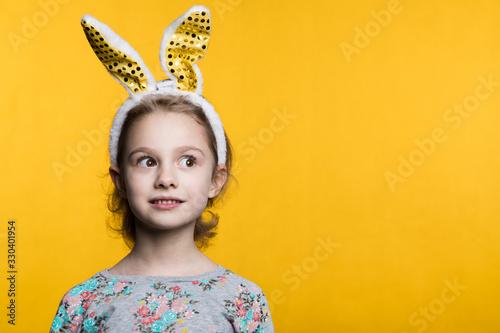 Obraz Cute little girl with bunny ears and basket full of Easter eggs - fototapety do salonu