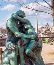 Bronze Statue The Kiss By Auguste Rodin (1882) In The Tuileries Garden With Egyptian Obelisk In Background - Paris, France