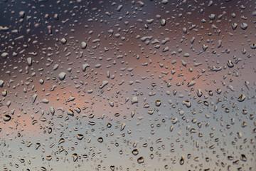 Okienna szyba pokryta kroplami deszczu.