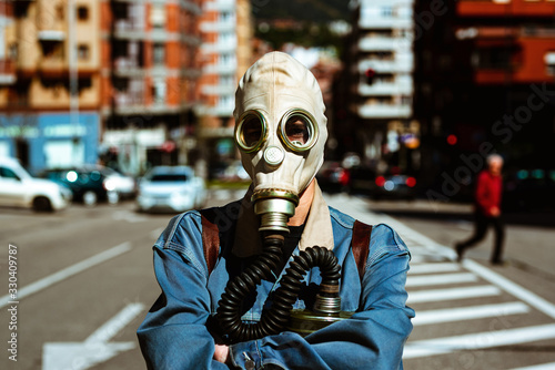 a person with his arms crossed, wears a gas mask and is in the middle of a city highway Canvas Print
